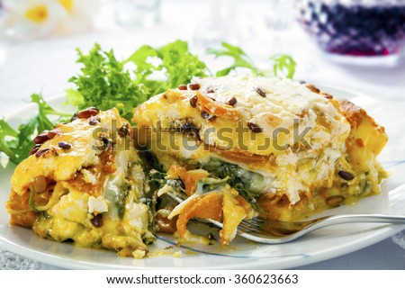 Vegetarian lasagna or lasagne.  Made with sweet potato, pumpkin, spinach and pine nuts. - stock photo
