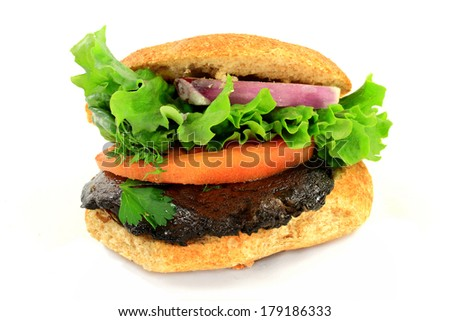 Vegetarian Organic Burger from Grilled Pre Marinated Portobello Mushroom, Slices of: Whole Grain Ban, Tomato and Red Onion, Garnished with Leaf of Lettuce and sprig of dill over white background  - stock photo