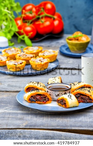 vegetarian pies with eggplant, red peppers, mushrooms with barbecue sauce. Picnic table with salty muffins, quiche, labneh,fresh tomatoes, mint on the old gray wood table on stone texture background - stock photo