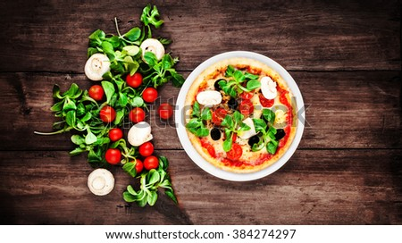 Vegetarian Pizza with vegetables on rustic wooden table top view image - stock photo