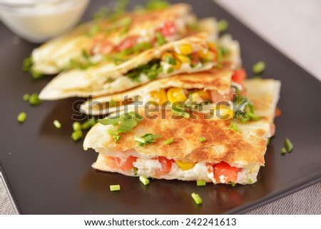 Vegetarian quesadilla with sour cream. Selective focus on the front wedge - stock photo