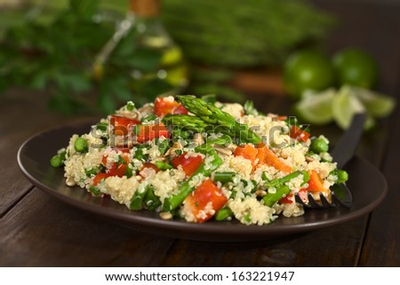 Vegetarian quinoa dish with green asparagus and red bell pepper, sprinkled with parsley and roasted sunflower seeds (Selective Focus, Focus on the asparagus heads on the dish)     - stock photo