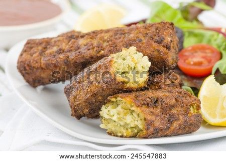 Vegetarian Sausage - Bubble and squeak sausages with salad and chili sauce. - stock photo