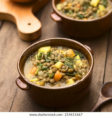 Vegetarian soup made of lentils, spinach, potato, carrot and onion served in dark brown bowls (Selective Focus, Focus one third into the soup) - stock photo