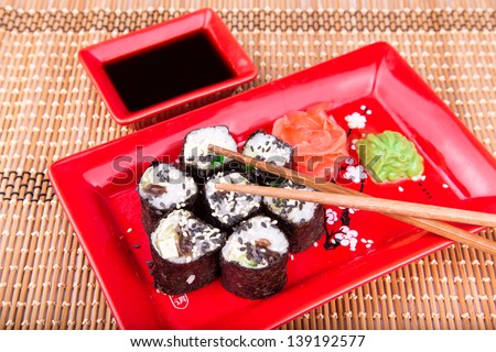 Vegetarian sushi roll served in a form of flower on a red plate on a bamboo mat - stock photo