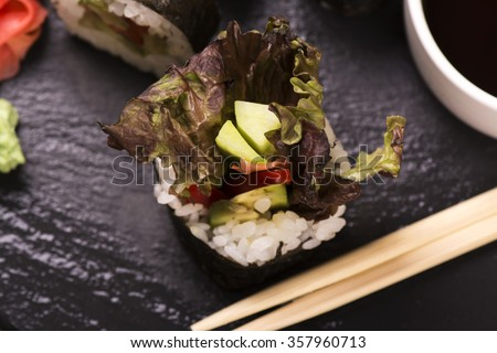 Vegetarian sushi roll served with wasabi, ginger and soy sauce over black stone background. Selective focus - stock photo