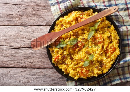 Vegetarian sweet rice with dried apricots and raisins close-up on the table. horizontal view from above