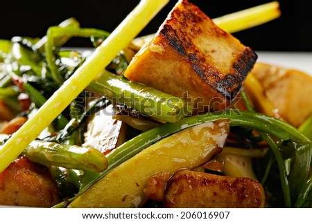 Vegetarian tofu meal prepared in frying pan served with greens and sauce closeup photo - stock photo