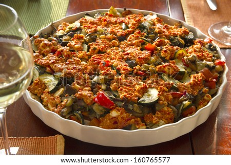 Vegetarian vegetable casserole with glass of white wine - stock photo