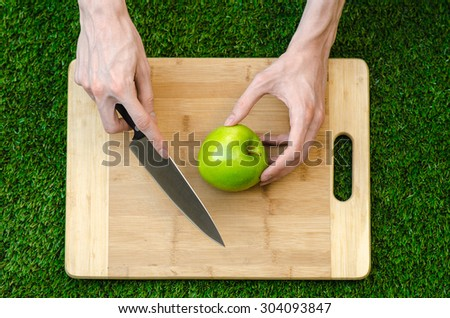 Vegetarians and cooking on the nature of the theme: human hand holding a knife and green apple on the background of a cutting board and green grass top view - stock photo