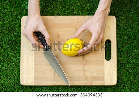 Vegetarians and cooking on the nature of the theme: human hand holding a knife and lemon yellow on the background of a cutting board and green grass top view - stock photo