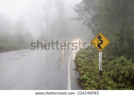 Vehicle driving on curved road in heavy fog  - stock photo