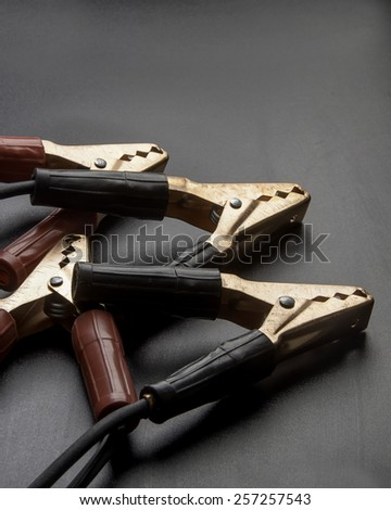 Vehicle jumper cables on a black surface/Jumper Cables/Well used clamp like battery jumper cables - stock photo