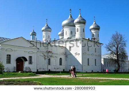 VELIKY NOVGOROD, RUSSIA - MAY 10, 2015:  Saviour Cathedral and parishioners walking along on the territory of Russian orthodox  Yuriev Monastery in spring sunny day - stock photo
