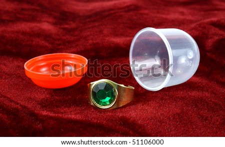 Vending machine jewelry ring with plastic container on a red velvet background - stock photo