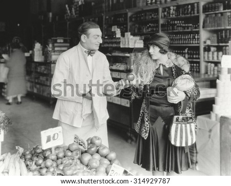 Vendor bargaining with woman at market - stock photo
