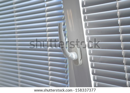 Venetian blinds on window, close up image focusing on window handle. - stock photo