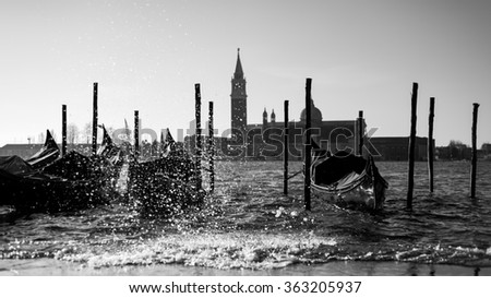 Venetian gondolas floating on The Grand Canal in the sunrise with splashing breaking waves, Venice, Italy, black and white image - stock photo