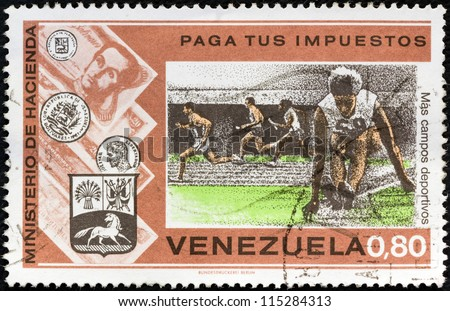 """VENEZUELA - CIRCA 1974: A stamp printed in Venezuela from the """"Pay Your Taxes Campaign"""" issue shows Sports stadium and athletes, circa 1974. - stock photo"""