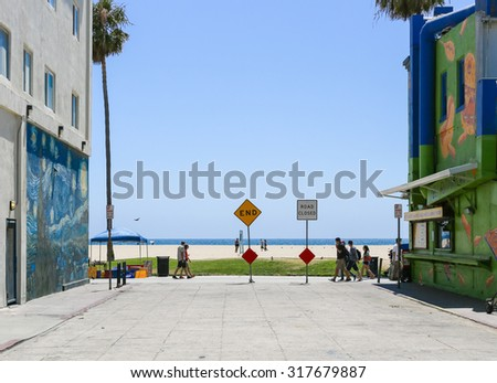 VENICE BEACH, USA - JUNE 4, 2014: A dead-end street between two houses in front of the pacific ocean with two signs saying End and Road closed. Behind it, people are walking on the Boardwalk. - stock photo