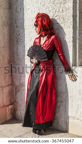 VENICE-FEB 18:Portrait of a person wearing a red and black disguise with a fan posing near a stone wall on February 18, 2012 in Venice. Venice Carnival is one of the biggest carnival in the world. - stock photo