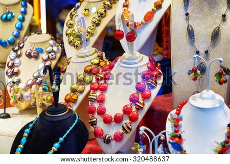 VENICE, ITALY - AUGUST 24, 2014: Colorful original jewelry from Murano Glass in shop window on the Rialto Bridge. Beautiful beads, necklaces and earrings. Venice is a popular tourist destination. - stock photo
