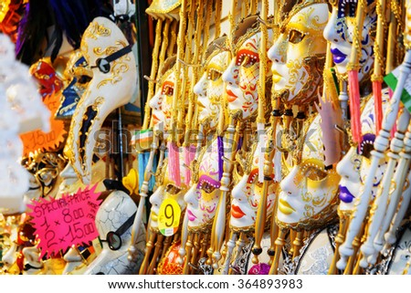 VENICE, ITALY - AUGUST 24, 2014: Side view of authentic and original Venetian full-face masks for Carnival. Ornate colorful and Plague Doctor masks in souvenir shop on the Rialto Bridge. - stock photo