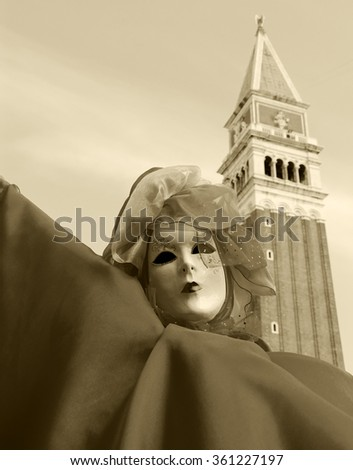 VENICE, ITALY - FEBRUARY 15, 2015:A mask at St Mark's Square and the bell tower of St Mark's Basilica at background. The Carnival in Venice is annual event which ends on Shrove Tuesday. - stock photo
