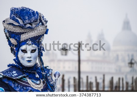VENICE, ITALY - 02 FEBRUARY 2016: Model dressed in blue and silver carnival costumes poses for photographers at the 2016 Venice Carnival, Italy - stock photo