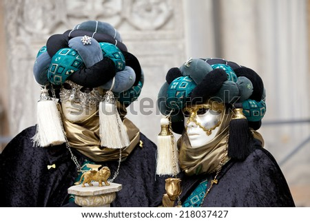 Venice, Italy - February 11 2012: People posing typical venetian carnival costume at the Carnival of Venice. Shot in St. Mark's Square.  - stock photo