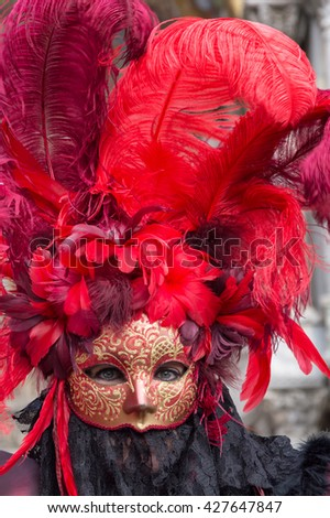 VENICE, ITALY - FEBRUARY 15, 2015: Portrait of an unidentified woman wearing a magnificent red costume at the Carnival of Venice, in Italy. - stock photo