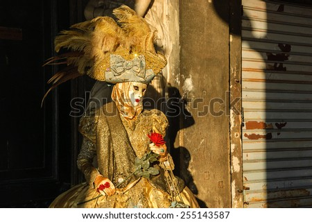 VENICE, ITALY - FEBRUARY 16, 2015: Romantic mask with red rose between sun rays and shadow on St Mark's Square during the Carnival. The Carnival in Venice is annual event which ends on Shrove Tuesday. - stock photo