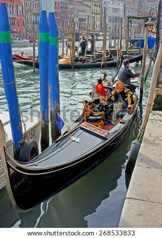 VENICE, ITALY-FEBRUARY 14, 2007: tourists with mask taking a gondola in a carnival day. Venice is a great tourists attraction with more than 27 million tourists every year. - stock photo