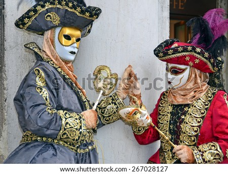 VENICE, ITALY - FEBRUARY 12: Two costumed ladies touching hands at the 2015 Venice Carnival:  February  12, 2015 in Venice, Italy - stock photo