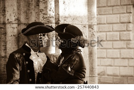 VENICE, ITALY - FEBRUARY 16, 2015:Two masks in St Mark's Square square during the traditional Carnival. The Carnival in Venice is annual event which ends on Shrove Tuesday. - stock photo