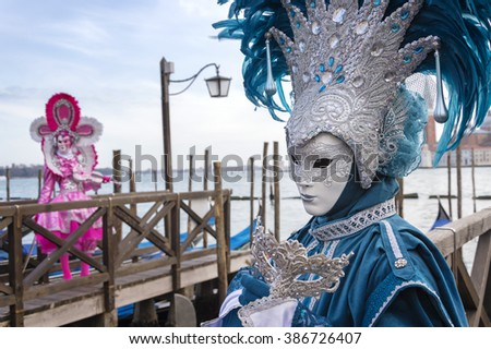 VENICE, ITALY - FEBRUARY 15, 2015:Two models disguised with colorful carnival costumes posing at a gondolas pier during the Carnival of Venice. - stock photo