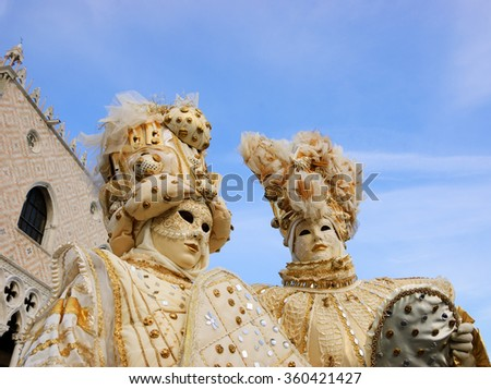 VENICE, ITALY - FEBRUARY 15, 2015:Two noble masks near Doge's Palace in St Mark's Square during traditional Carnival. The Carnival in Venice is annual event which ends on Shrove Tuesday. - stock photo