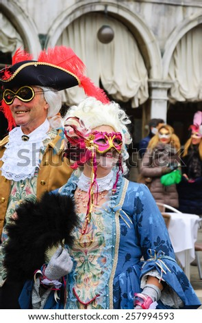VENICE, ITALY - FEBRUARY 14, 2015:Two seniors in masks at St Mark's Square during traditional Carnival. The Carnival in Venice is annual event which ends on Shrove Tuesday. - stock photo