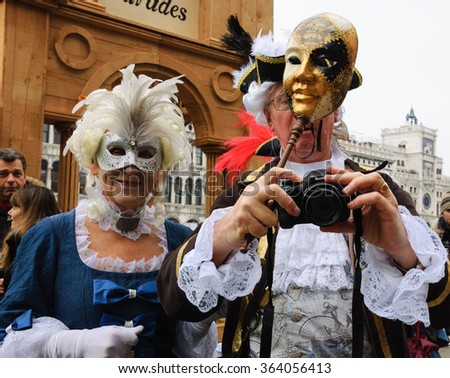 VENICE, ITALY - FEBRUARY 14, 2015:Two seniors in masks taking photo at St Mark's Square during traditional Carnival. The Carnival in Venice is annual event which ends on Shrove Tuesday. - stock photo