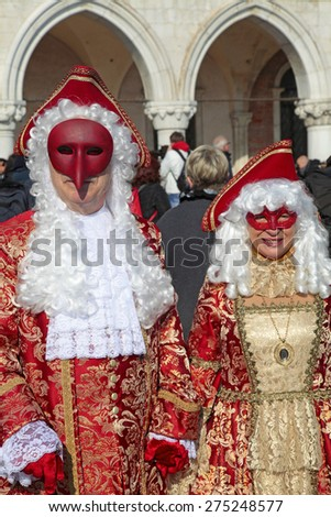 VENICE, ITALY - FEBRUARY 8, 2015: Two unidentified masked persons in magnificent red and gold costume on San Marco Square during the Carnival in Venice, Italy.  - stock photo