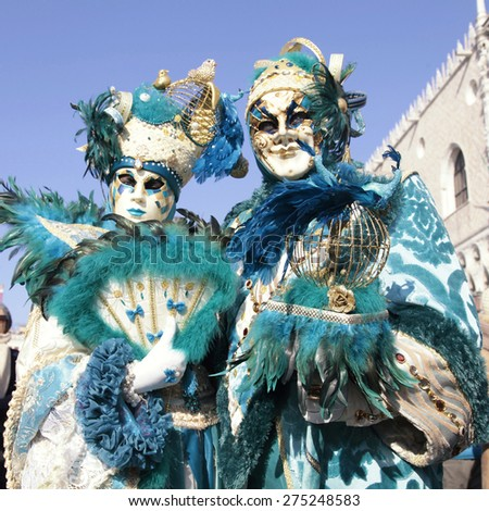 VENICE, ITALY - FEBRUARY 8, 2015: Two unidentified masked persons in magnificent turquoise costume on San Marco Square during the Carnival in Venice, Italy. Square image - stock photo