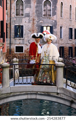 VENICE, ITALY - FEBRUARY 16, 2015: Unidentified mid-aged couple in traditional carnival costumes on little bridge over the canal. The Carnival in Venice is annual event which ends on Shrove Tuesday. - stock photo