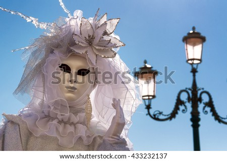 VENICE, ITALY - FEBRUARY 16, 2015: Venetian mask posing with a traditional venetian lamp on the background - stock photo