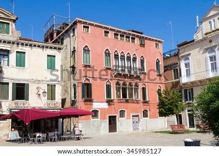 VENICE, ITALY: JULY 18 2014: A cafe next to a four story pink building - stock photo