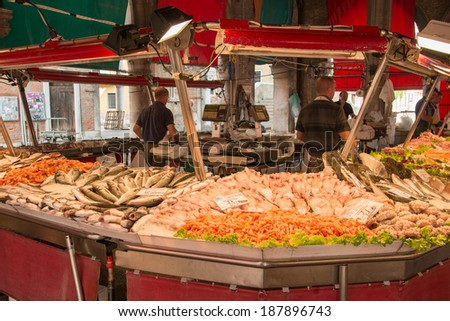 VENICE, ITALY - JUNE 17: Fish stand on famous Rialto market in Venice on June 17, 2013. Market workers selling various fish and seafood in the morning  - stock photo