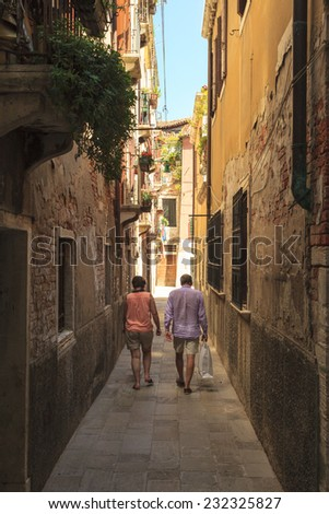 VENICE, ITALY - 1 JUNE, 2014: Narrow street in the old town of Venice, where countless small souvenir and art shops offers gifts, artworks and cheep souvenirs for the visitors of Venice. - stock photo