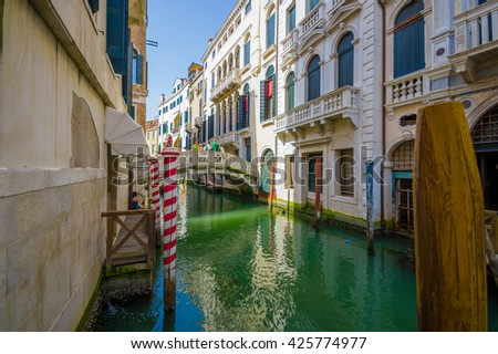 VENICE, ITALY - JUNE 18, 2015: Sun ray illuminating a beautiful historic house and white bridge, tourisit visitting Venice. - stock photo