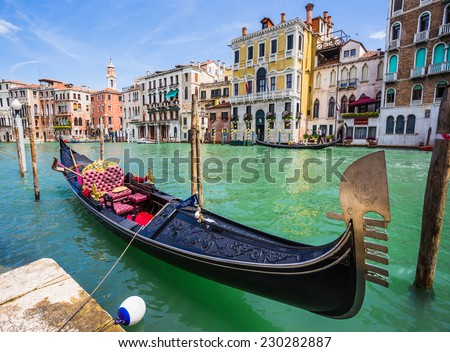 VENICE, ITALY - JUNE 26: Tourists travel on gondolas at canal on June 26, 2014 in Venice, Italy . Gondola trip is the most popular touristic activity in Venice. - stock photo