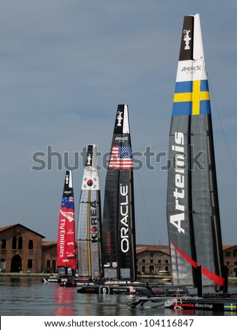VENICE, ITALY - MAY 15: Four catamarans AC45 in the team bases area waiting for a new test in the Venice lagoon during the America's Cup previous races days in May 15, 2012 in Venice, Italy. - stock photo