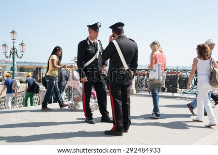 VENICE, ITALY-MAY 11: Two Carabinieri, from one of Italy's two uniformed  police forces provide travelers with security keeping a watch on activities as tourists pass by May 11, 2011 in Venice, Italy - stock photo